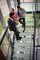Business people using digital tablet in building office. Business people standing on stairs.