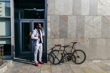 Trendy man talking smartphone on urban background