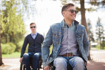 Shot of a young man spending time in a park with his friend using a wheelchair