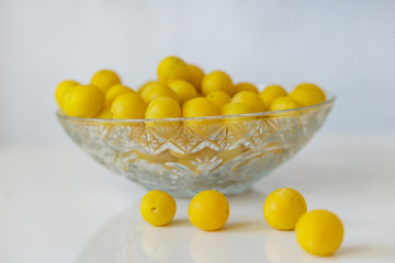 Close-up of a crystal bowl of ripe yellow plums on a white background. Concept Healthy Eating, Seasonal Fruit.