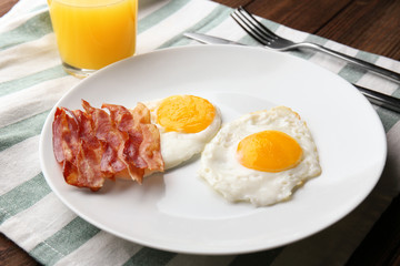 Fond de hotte en verre imprimé Ouf Plate with fried eggs and bacon on table
