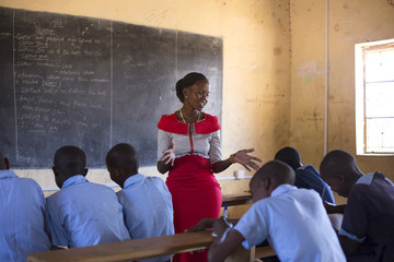 Female school teacher, teaching school children, Kenya, Africa.