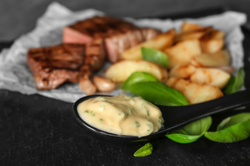 Spoon with delicious sauce for steak on table, closeup