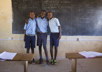 Three smiling school boys in classroom. Kenya, Africa.