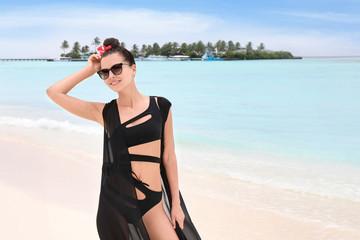 Beautiful young woman on beach at sea resort