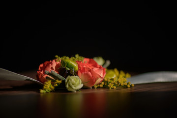 Wedding floral centerpiece with red rose at its core against a dark background.