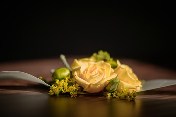 Wedding floral centerpiece with yellow rose at its core against a dark background.