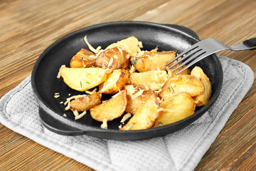Delicious potato with cheese in frying pan on pot holder on table