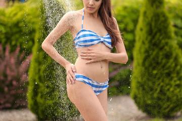 Beautiful young woman taking shower outdoors