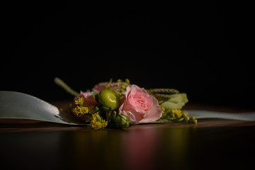 Wedding floral centerpiece with pink rose at its core against a dark background.