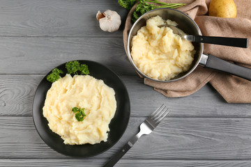 Plate and pot with mashed potatoes on wooden background