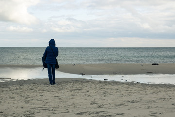 A lonely girl is standing on an empty beach and looking at the sea in the fall