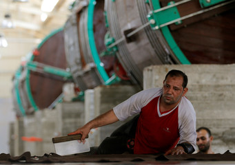 A worker removes impurities on leather in the factory of Al Rowad Leather Tannery at El Robbiki Leather City in Badr City