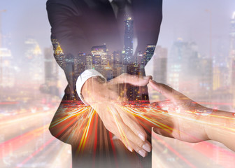 Double exposure of businessman will handshaking for business relationship, light trails street and city in the night as Commitment and Partnership concept.