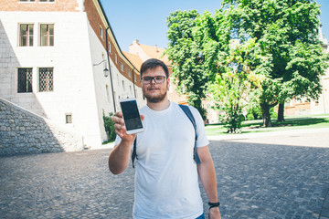 Handsome guy in white t-shirt is holding a smartphone,