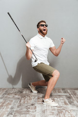 Full length image of a Screaming golfer in sunglasses