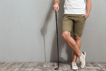 Cropped image of golfer posing with club