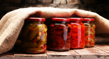 Jar with variety of pickled vegetables. Carrots, field garlic, parsley in glas. Preserved food. Fermented preserved vegetarian food concept. Canned food