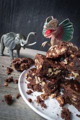 walnut brownies stacked on plate with dinosaur and elephant