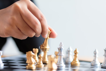 Close up shot hand of business woman moving golden chess to defeat a silver king chess on white and black chess board for business challenge competition winner and loser concept