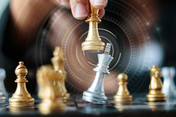 Close up shot hand of business woman moving golden chess to defeat and kill silver king chess on white and black chess board for business challenge competition winner and loser concept
