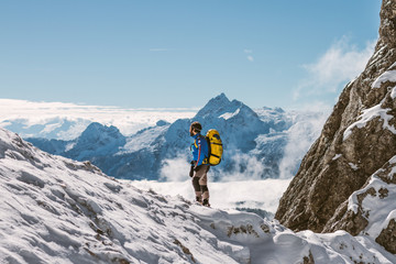 male mountaineer with yellow backpack overlooking snowcovered mo