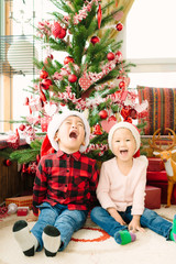 Girl and boy laughing under Christmas tree