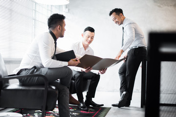 Young Asian entrepreneurs discussing ideas in the office.