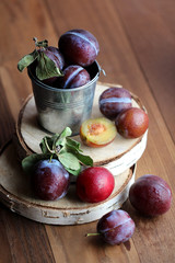 Plums in a small bucket on a wooden background