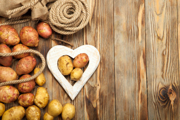 Potatoes and heart on a wooden background