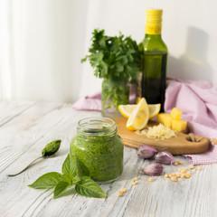 Bank of pesto sauce on white kitchen table on a light background.