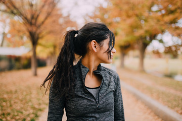 A young woman sitting on a park bench after a workout