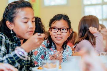 Kindergarten kids eating at school canteen
