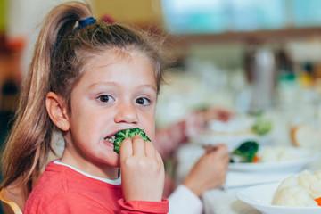 Funny kid eating healthy food at school