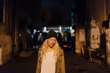 Beautiful blonde woman walking at night