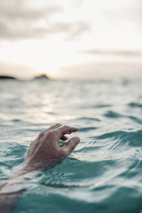 A man's hand on the seascape at sunset