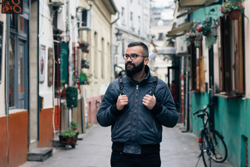 Portrait of a male model with glasses on the street