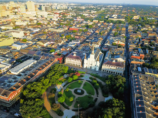 Aerial view of Jackson Square with Saint Louis Cathedral church and surround extant historical buildings from French Quarter and downtown skylines on the left in morning. New Orleans travel background