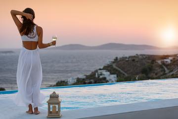 Elegante Frau in weißem Kleid genießt den Sonnenuntergang mit einem Glas Wein