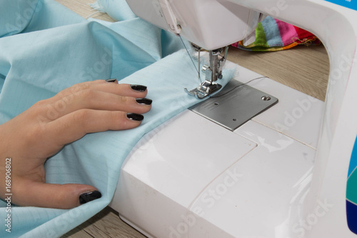 ad89c5a0877c0 seamstress female sews clothes and put thread in needle. Workplace of tailor.  people, needlework and tailoring concept - tailor threading needle of sewing  ...