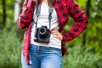 Female wearing plaid shirt holding the camera around her neck