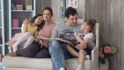 Happy family is reading a book to children. Mom and Dad read fairy tales to two daughters