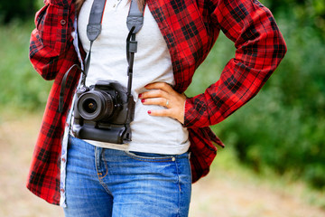 Female wearing plaid shirt holding the camera around her neck
