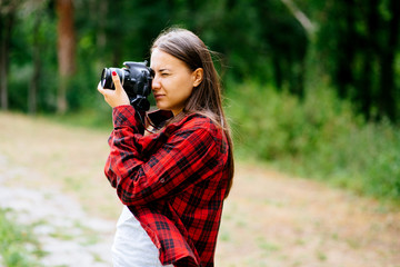 White girl wearing plaid shirt holding camera in the forest