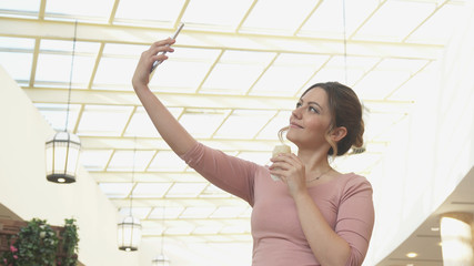Attractive young woman doing selfie and eating ice cream at the Mall