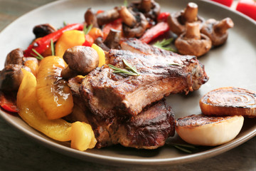 Plate with tasty grilled steak and vegetables on table, close up