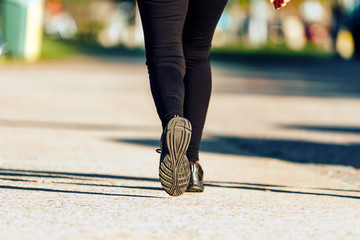 Woman's legs with leggings and sneakers walking along a path
