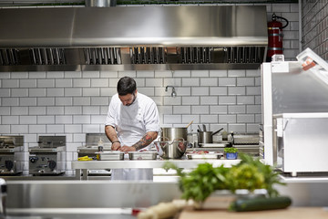 Male Chef Preparing Food In Commercial Kitchen