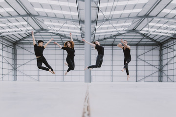 Four dancers jumping in the air in unison in a large spacious empty warehouse