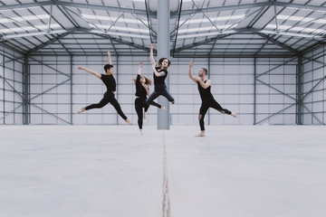 Four dancers jumping at staggered heights in a large empty warehouse